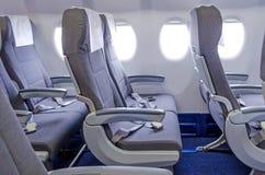 Кресла в кабине пассажира, с ремнями безопасности и иллюминаторами Стоковые Изображения