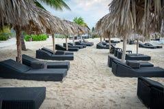 Кресла для отдыха кроватей Солнца и зонтики крыши соломы соломы на тропическом пляже стоковая фотография