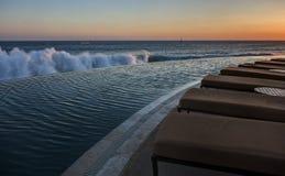 Кресла для отдыха пейзажным бассейном и Тихим океаном на заходе солнца стоковая фотография rf