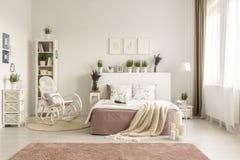 Кресло-качалка рядом с кроватью с одеялом в просторном белом интерьере спальни с розовым ковром Реальное фото стоковое изображение