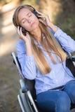Кресло-коляска молодой женщины слушая к музыке Стоковые Изображения RF