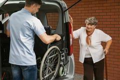 Кресло-коляска удерживания попечителя в автомобиле стоковое фото