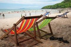 Кресло 4 пляжей с кожаными тапочками с туристами на песчаном пляже стоковая фотография