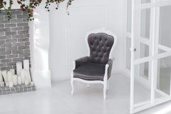 Кресло черно-белых велюров винтажное в minimalistic скандинавской комнате с камином и свечами кирпича горизонтально Стоковое Изображение RF