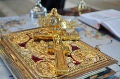 Кресты, кольца и кроны золота на таблице внутри   Стоковые Фото