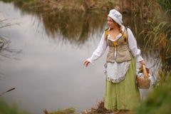 Крестьянская женщина идет рекой Стоковые Изображения