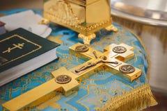 Крестящ в церков, золотые религиозные утвари: библия, крест, молитвенник, missal Детали в правоверной христианской церков Стоковое фото RF
