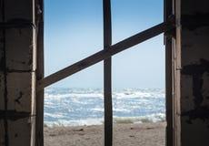 Крест доск в окне обозревая море и пляж стоковое фото rf