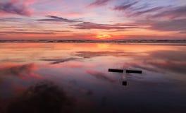 Крест пляжа красного захода солнца влажный Стоковая Фотография RF