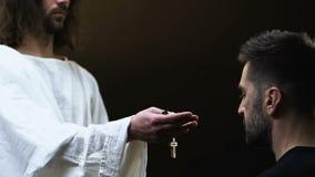 Крест удерживания Иисуса, достигающ вне руку к молитве, делая удовлетворение для грехов акции видеоматериалы