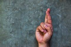 Крест one пальцы жест рукой обыкновенно используемый для того чтобы пожелать везение стоковые изображения