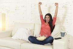 Кресло софы женщины дома смотря excited спорт футбола ТВ отпраздновать победу Стоковая Фотография RF