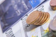 Кредитки и монетки евро финансы яичка диетпитания принципиальной схемы предпосылки золотистые Стоковое Фото