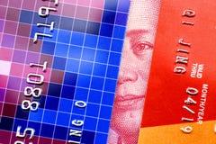 Кредитная карточка и 100 юаней фарфора Maozedong смотря прищурясь между 2 кредитными карточками Стоковые Изображения