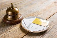 Кредитная карточка для оплачивать, кольца кельнера и проверки на предпосылке стола кафа деревянной Стоковые Фото