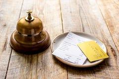 Кредитная карточка для оплачивать, кольца кельнера и проверки на предпосылке стола кафа деревянной Стоковая Фотография