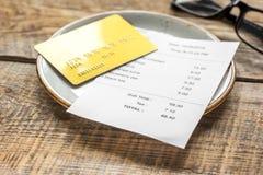 Кредитная карточка для оплачивать, плиты, стекел и проверки на предпосылке стола кафа Стоковые Фотографии RF
