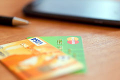 2 кредитные карточки, ручка и телефона на таблице сфокусируйте мягко Стоковое Изображение