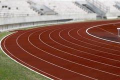 Кривая следа стадиона атлетики идущая на стадионе спорта Стоковая Фотография RF