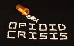 Кризис Opioid сказал по буквам вне с с белыми пилюльками на черной предпосылке с разлитыми пилюльками над словами Стоковые Изображения