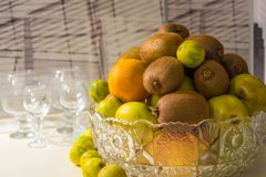 Кристаллическая ваза с плодоовощами: киви, известка, апельсин, яблоко Стоковые Фото