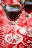 2 кристаллических стекла красного вина, красной предпосылки, крупного плана Стоковые Изображения RF