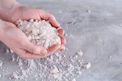 Кристаллы соли моря в руке женщин на белой предпосылке, надземной, конце-вверх стоковые фото