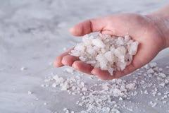Кристаллы соли моря в руке женщин на белой предпосылке, надземной, конце-вверх стоковая фотография rf