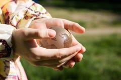 Кристаллический глобус в ладонях ` s детей Стоковое Фото