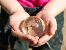 Кристаллический глобус в ладонях ` s детей Стоковая Фотография