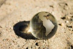 Кристаллический глобус лежит на песке Стоковые Изображения