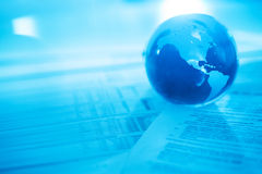 Кристаллический глобус на финансовых документах Стоковая Фотография