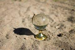 Кристаллический глобус стоит на песке Стоковое фото RF