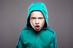 Кричащий мальчик в клобуке смешной ребенк гримасы стоковое фото