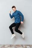 Кричащий молодой человек стоя над серой стеной и скакать стоковая фотография
