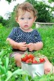 Кровати сада около маленькой девочки сидят, и близко она Стоковая Фотография