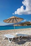 Кровати Солнця и зонтик солнца на пустом море приставают к берегу на живописных камешках среднеземноморского Стоковая Фотография
