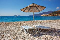 Кровати Солнця и зонтик солнца на пустом море приставают к берегу на живописных камешках среднеземноморского Стоковое фото RF