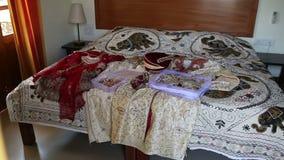 Кровать крупного плана большая с индийскими платьями и украшениями свадьбы