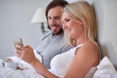 Кровать мобильного телефона пар Стоковая Фотография
