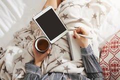 Кровать мой офис Высокая угловая съемка девушки лежа в уютной атмосфере, слушая музыке в наушниках, держа таблетку и Стоковое Изображение
