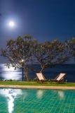 Кровать Солнця около бассейна на nighttime Стоковое фото RF