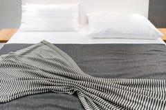 Кровать с striped крышкой и белыми подушками Стоковое Изображение RF