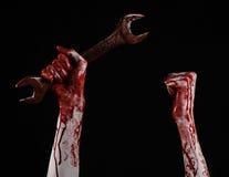 Кровопролитная рука держа большой ключ, кровопролитный ключ, большой ключ, кровопролитную тему, тему хеллоуина, шальной механика, Стоковое Фото