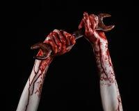 Кровопролитная рука держа большой ключ, кровопролитный ключ, большой ключ, кровопролитную тему, тему хеллоуина, шальной механика, Стоковая Фотография RF