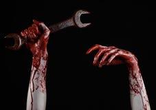 Кровопролитная рука держа большой ключ, кровопролитный ключ, большой ключ, кровопролитную тему, тему хеллоуина, шальной механика, Стоковые Изображения RF