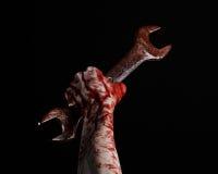 Кровопролитная рука держа большой ключ, кровопролитный ключ, большой ключ, кровопролитную тему, тему хеллоуина, шальной механика, Стоковое Изображение
