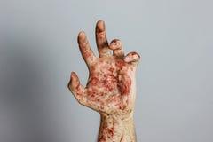 Кровопролитная рука перед серой предпосылкой стоковое фото rf