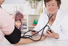 Кровяное давление старшего женского доктора измеряя с пациентом стоковые изображения rf