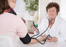 Кровяное давление старшего женского доктора измеряя с пациентом стоковые изображения